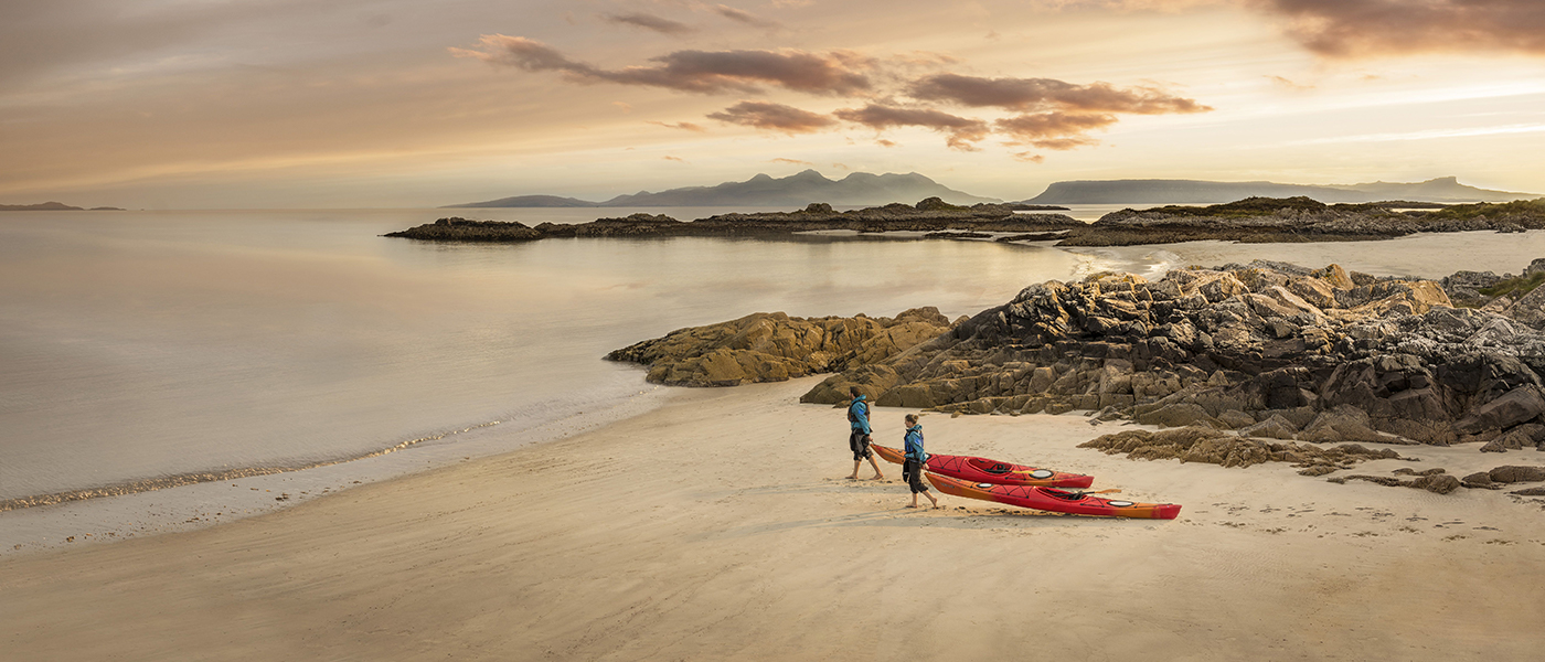 Two people with kayaks on Camusdarach beach